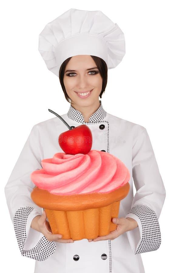De Chef-kok Holding Huge Cupcake van het vrouwengebakje stock afbeelding