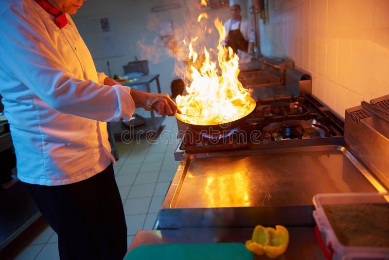De chef-kok in hotelkeuken bereidt voedsel met brand voor stock afbeeldingen