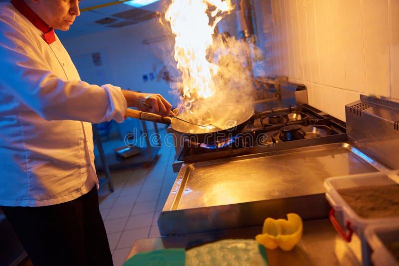 De chef-kok in hotelkeuken bereidt voedsel met brand voor stock foto
