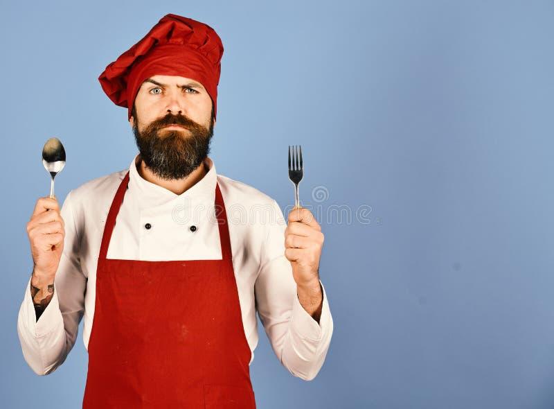 De chef-kok houdt bestek Kok met ernstig gezicht in eenvormig Bourgondië royalty-vrije stock afbeeldingen