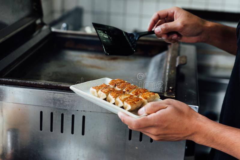 De chef-kok houdt een plaat van yaki-Gyoza reeks Japans Pan-Fried Dumplings na gekookt Heet, vers, sappig en smakelijk stock foto