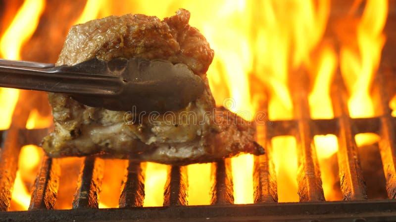 De chef-kok keert meerdere keren het geroosterde lapje vlees met tang om en bekijkt hoeveel hij gebraden was stock afbeelding