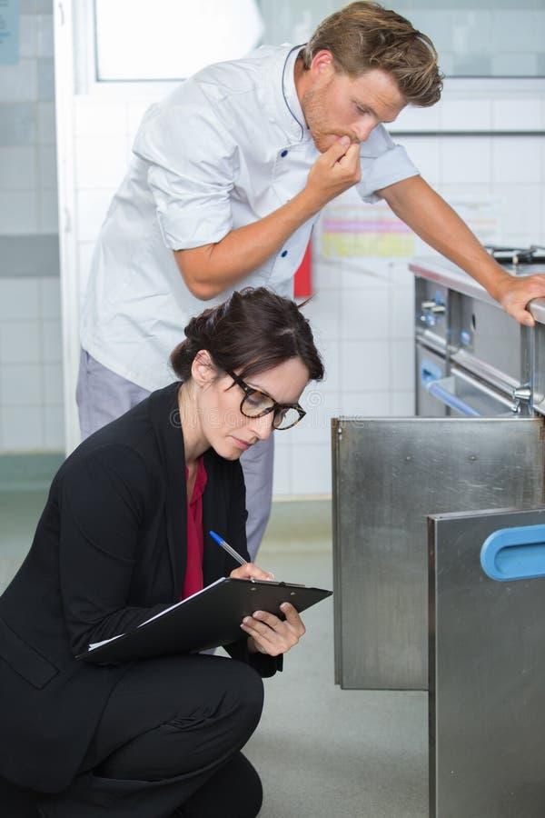 De chef-kok kijken die die als inspecteur wordt betroffen kijkt in oven stock afbeeldingen