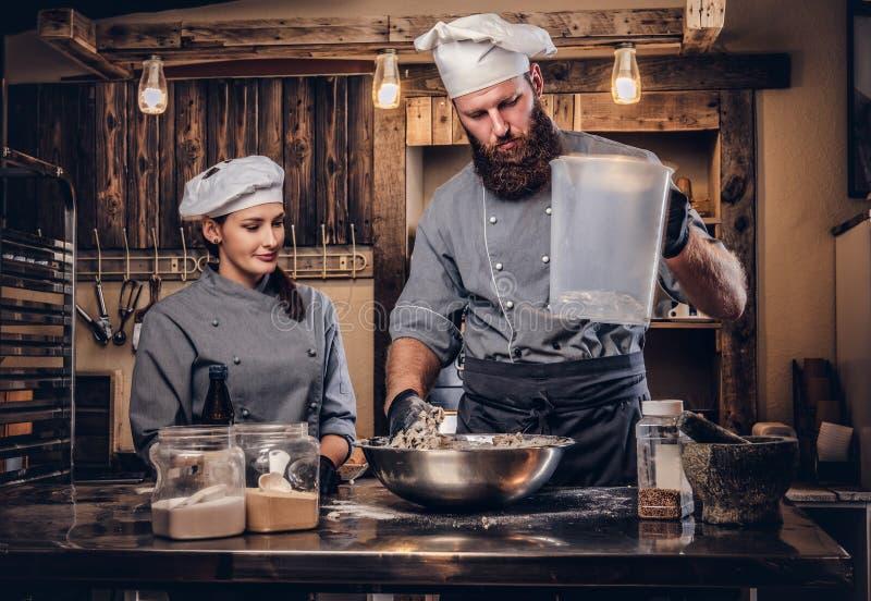 De chef-kok mengt de ingrediënten voor het deeg Chef-kok die zijn medewerker onderwijzen om brood in de bakkerij te bakken royalty-vrije stock fotografie