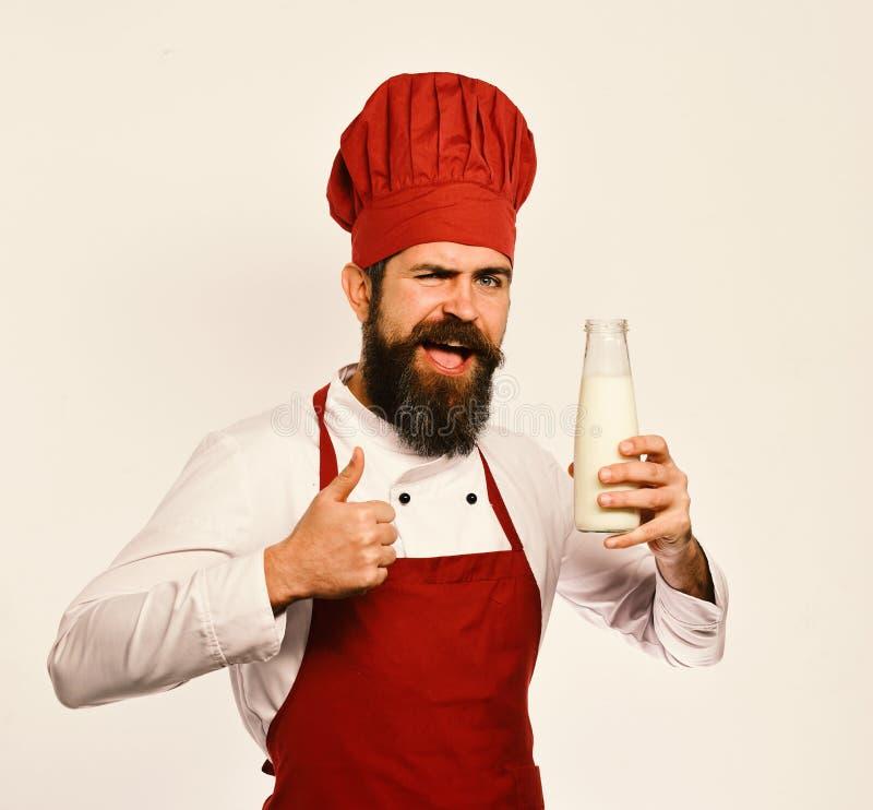 De chef-kok met milkshake of yoghurt toont duimen royalty-vrije stock foto