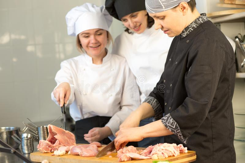 De chef-kok onderwijst stagiair een groep mensen om een kip te snijden Hoofdklasse op de achtergrond van de keuken royalty-vrije stock fotografie