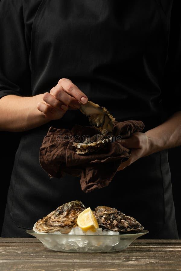 De chef-kok opent een oester op een achtergrond van witte wijn, sla, citroenen en kalk royalty-vrije stock foto