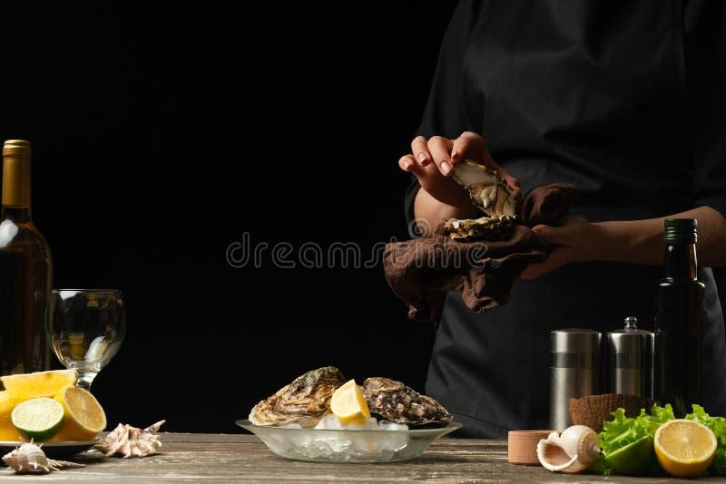 De chef-kok opent een oester op een achtergrond van witte wijn, sla, citroenen en kalk Met ruimte voor een inschrijving stock foto