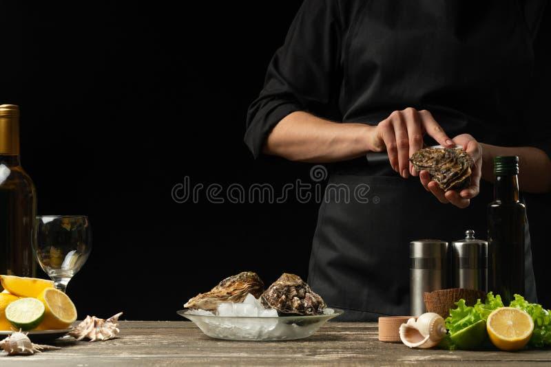 De chef-kok opent het mes en maakt de ruwe oester, op de achtergrond van witte wijn, sla, citroenen en kalk schoon Met ruimte voo royalty-vrije stock foto