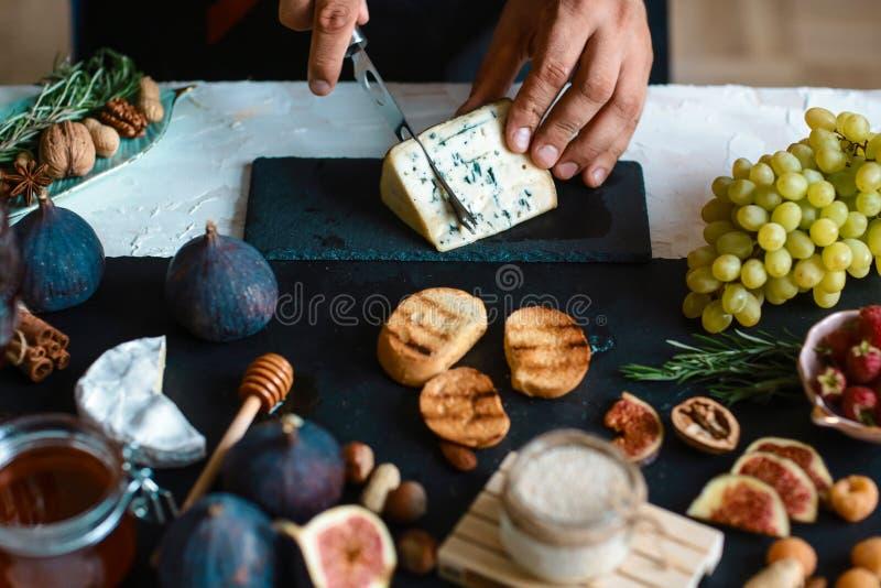 De chef-kok overhandigt het koken bruschetta van kaas, fig. en honing Ruwe ingrediënten voor het koken van gezonde snacks, goed v royalty-vrije stock afbeeldingen