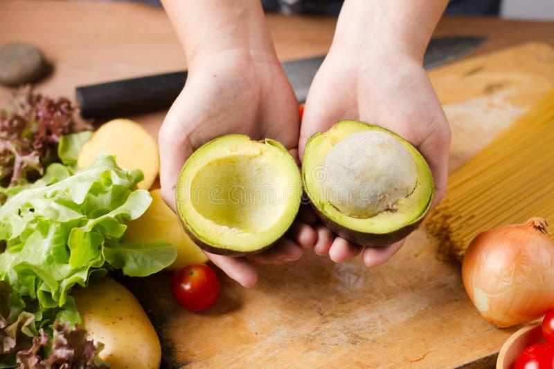 De chef-kok sneed avocado voorbereidingen treft voor maakt een plantaardige salade royalty-vrije stock foto's