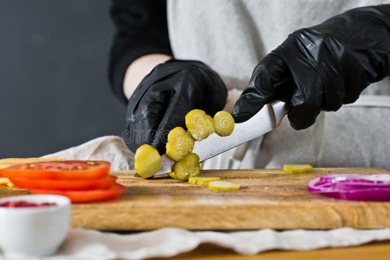 De chef-kok snijdt groenten in het zuur r Eigengemaakt hamburgerrecept Keuken, zijaanzicht, ruimte voor tekst stock foto