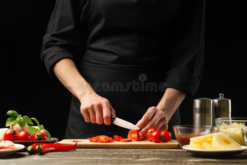 De chef-kok snijdt kersentomaten met groenten Voor de voorbereiding van pizza, tomatensaus, salade Een heerlijk maaltijdconcept, royalty-vrije stock foto