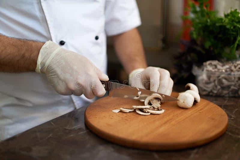 De chef-kok snijdt paddestoelen op een houten raad royalty-vrije stock afbeeldingen