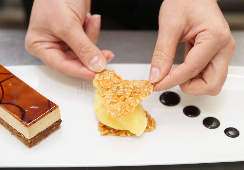 De chef-kok van het gebakje verfraait een dessert royalty-vrije stock fotografie