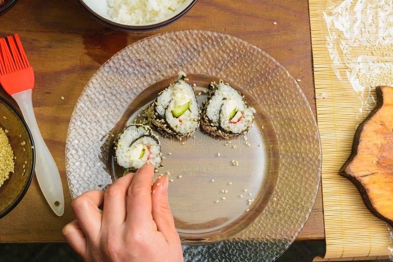 De chef-kok van het restaurant smeert de borstel van de saus op de rol van sushi in royalty-vrije stock foto's