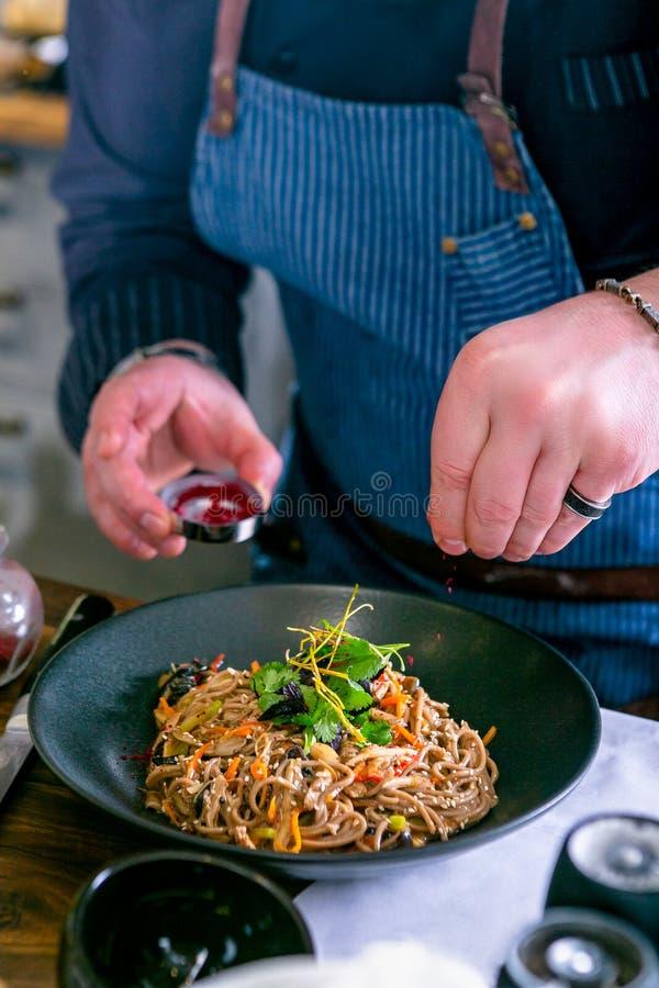 De chef-kok verfraait de boekweitnoedels met eend en paddestoel Hoofdklasse in de keuken Het proces om te koken Stap voor stap stock afbeelding