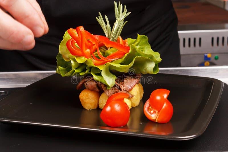 De chef-kok versiert smakelijke schotel royalty-vrije stock afbeeldingen