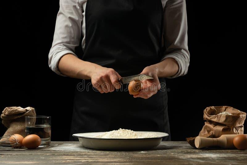 De chef-kok werkt met deeg, breekt het ei en ranselt, voor de voorbereiding van focaccia, Italiaanse deegwaren, pizza of brood Vo stock foto