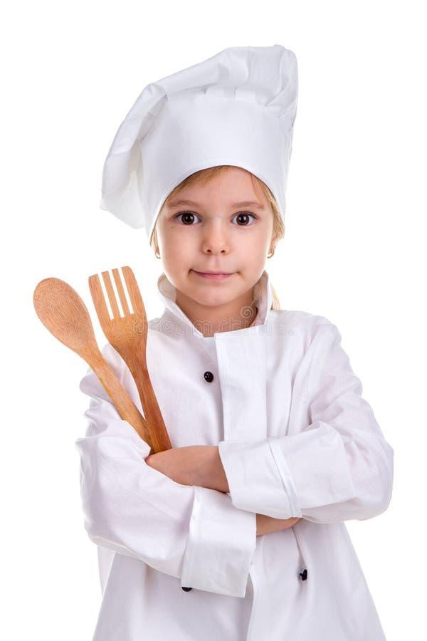 De chef-kok witte eenvormig van het Smirkingsmeisje geïsoleerd op witte achtergrond Het houden van houten lepel en vork in de gev stock afbeelding