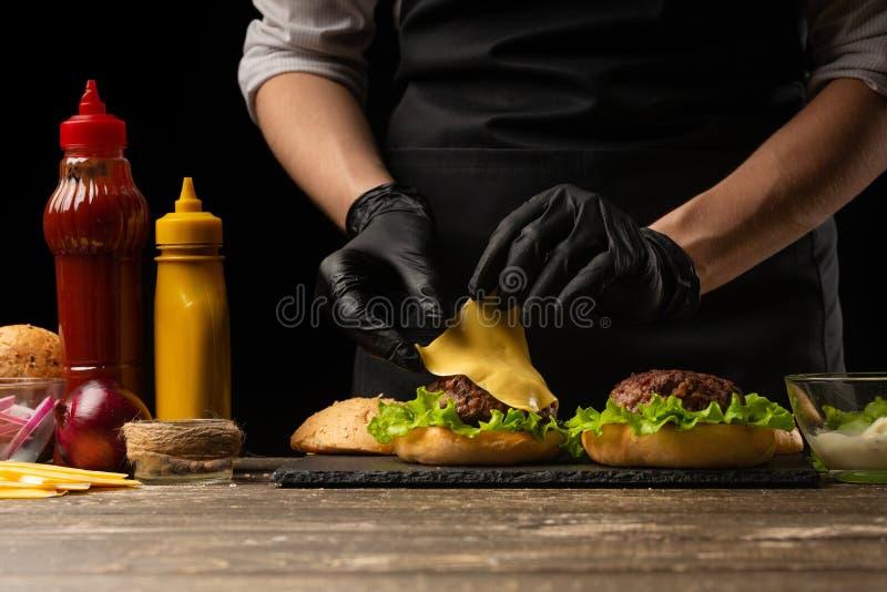 De chef-kok zet de kaas op een hamburger, op de achtergrond van de ingrediënten stock foto
