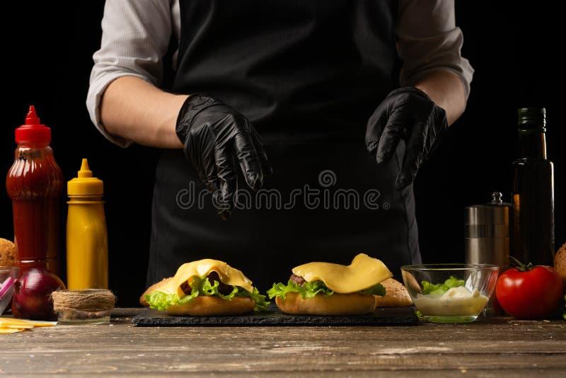 De chef-kok zet de kaas op een hamburger, op de achtergrond van de ingrediënten Horizontale foto, Smakelijk en ongezond voedsel,  royalty-vrije stock afbeeldingen