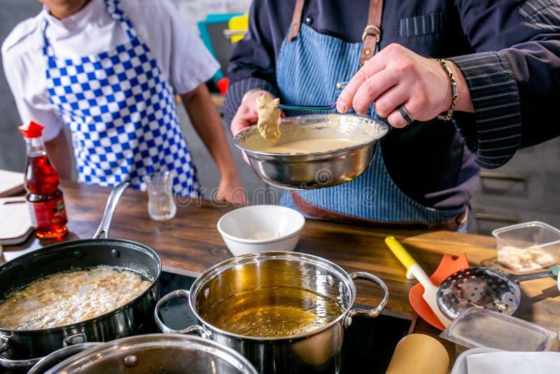 De chef-kok zet de plakken van vissen met beslag in de pan met boter Hoofdklasse in de keuken Het proces om te koken Stap voor st royalty-vrije stock fotografie