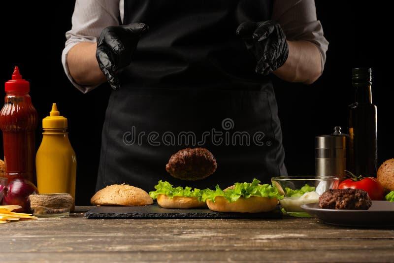 De chef-kok zet rundvleespasteitje op een hamburgerbrood, tegen de achtergrond van de ingrediënten stock foto