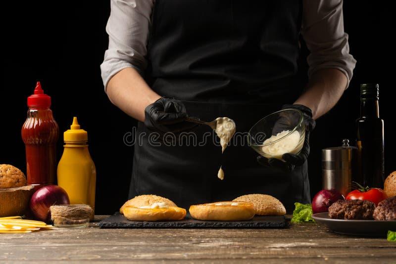 De chef-kok zet saus op een hamburgerbrood, tegen de achtergrond van ingrediënten Heerlijk en schadelijk voedsel, snel voedsel, e royalty-vrije stock afbeelding