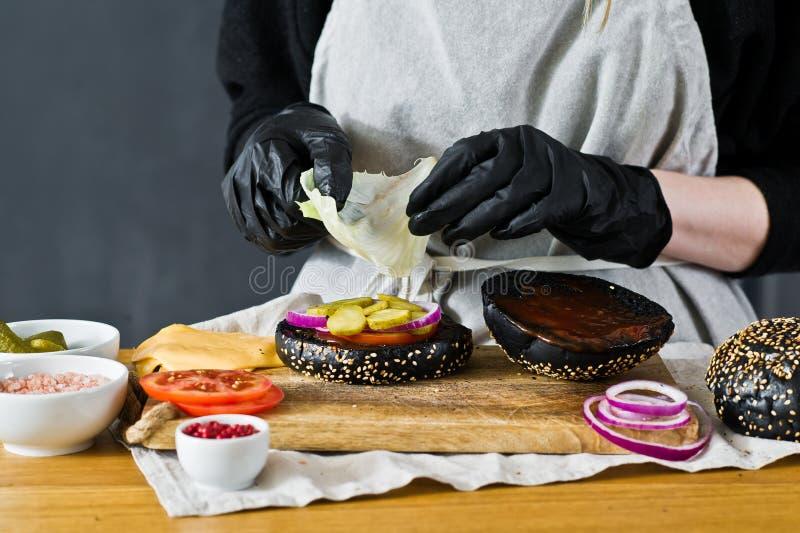 De chef-kok zet sla op een cheeseburger r Eigengemaakt hamburgerrecept stock afbeelding