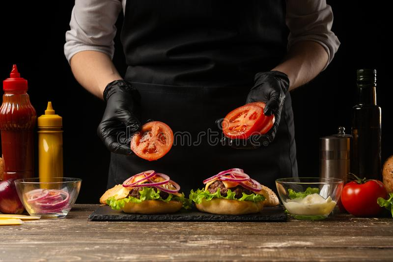 De chef-kok zet tomatenringen op een hamburger, op de achtergrond van de ingrediënten Horizontale foto, Smakelijk en ongezond voe stock foto's