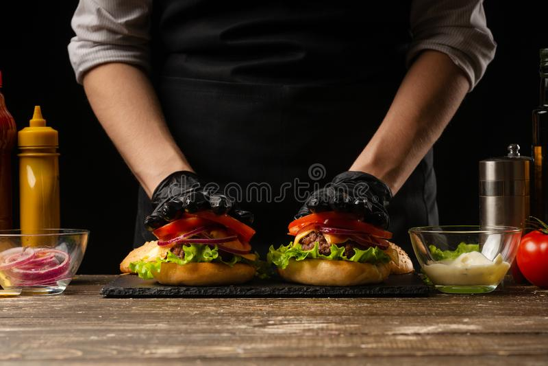 De chef-kok zet tomatenringen op een hamburger, op de achtergrond van de ingrediënten Horizontale foto, Smakelijk en ongezond voe stock foto