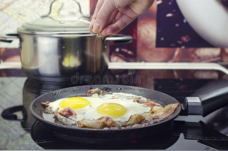 De chef-kok zout de gebraden eieren in een pan, kookt het bacon en de gebraden eieren in de pan, die in de keuken koken, zet royalty-vrije stock foto