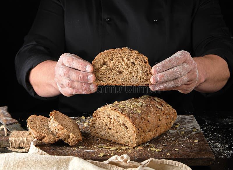 de chef-kok in zwart eenvormig levensonderhoud sneed een stuk van gebakken brood van roggebloem en pompoenzaden af royalty-vrije stock foto's