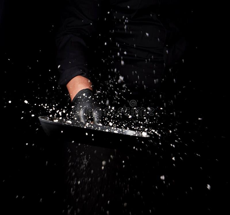 De chef-kok in zwarte eenvormig houdt een pan met wit zout en werpt omhoog stock foto's