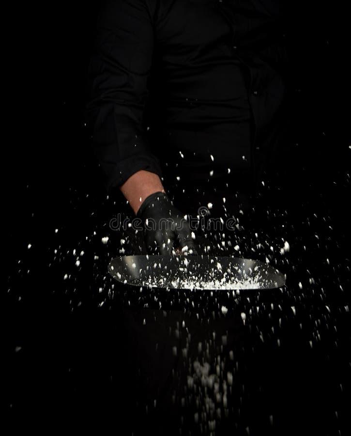 De chef-kok in zwarte eenvormig houdt een pan met wit zout en werpt omhoog stock foto