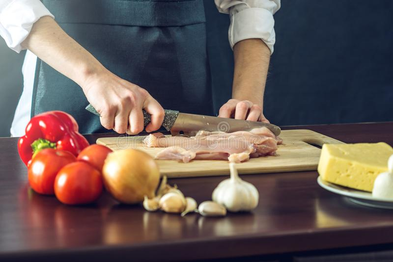 De chef-kok in zwarte schort snijdt het mes van de kippenfilet Concept milieuvriendelijke producten voor het koken royalty-vrije stock afbeeldingen