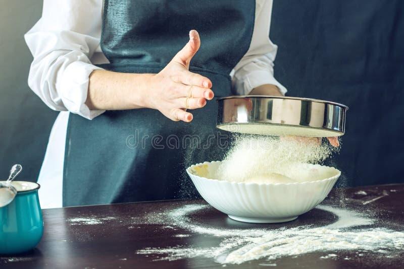 De chef-kok in zwarte schort zift de bloem door een zeef om het deeg voor pizza voor te bereiden stock afbeeldingen