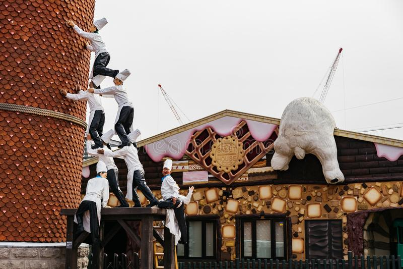 De chef-kokbeeldhouwwerken verbinden aan anderen om de gehelde bouw te leunen en het beklimmen het wit draagt bij het Park van Sh stock foto