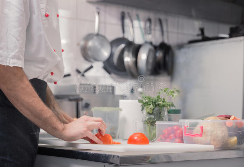 De chef-kokkeuken van close-uphanden, scherpe tomaten stock afbeeldingen