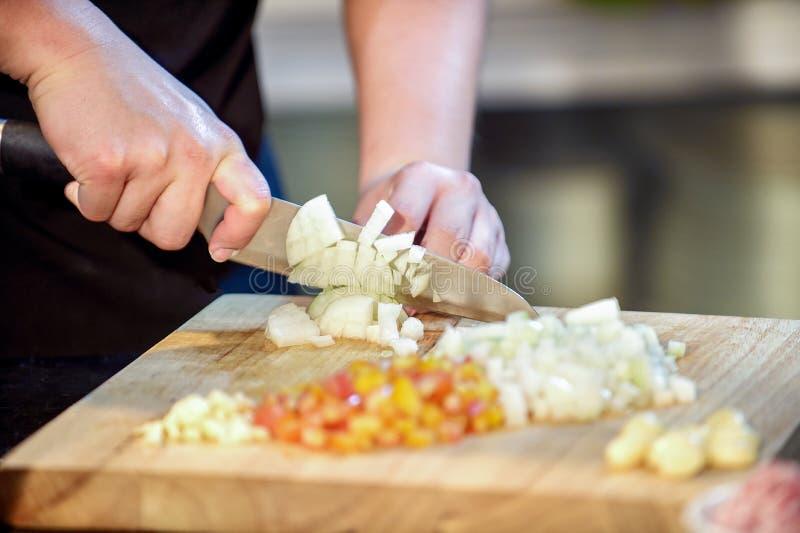 De chef-kokknipsel van de close-uphand omhoog een ui met een mes aan boord stock foto