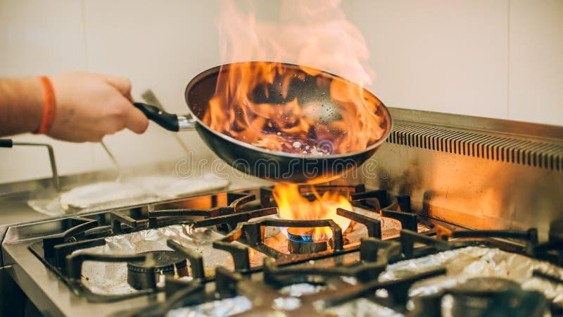 De chef-kokkok bereidt maaltijd in de brandwondpan van de vlambrand voor stock afbeeldingen