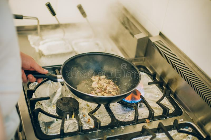 De chef-kokkok bereidt maaltijd op pan in de keuken voor stock foto's