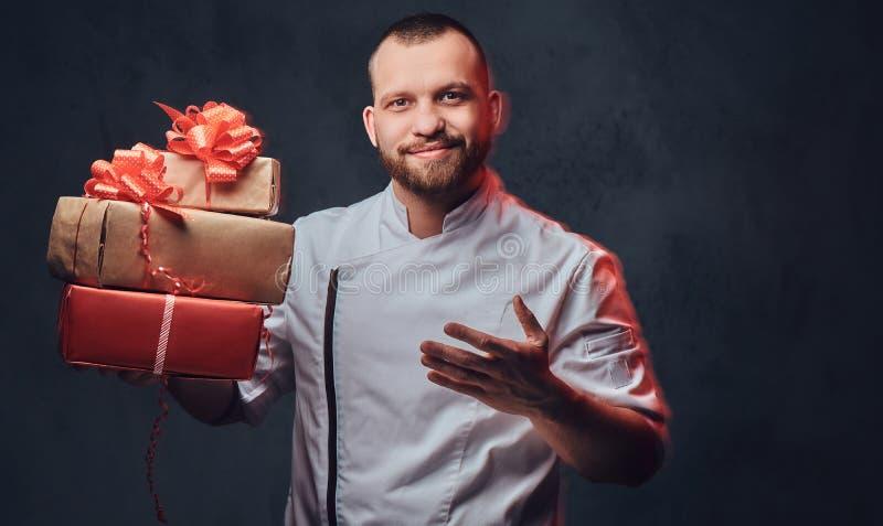 De chef-kokkok houdt kleurrijke document Kerstmisgiften royalty-vrije stock foto