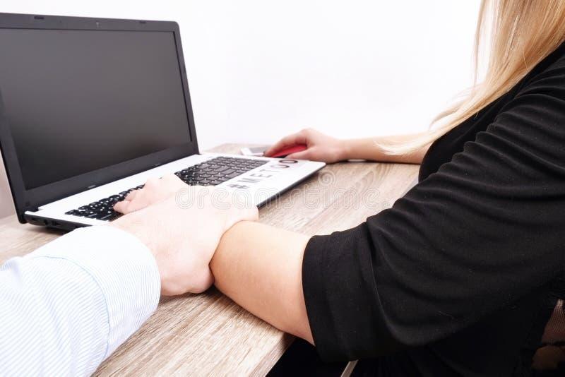 De chef- man toont ongepast gedrag naar jonge vrouw bij werkplaatsbureau De hevige mannelijke grepen tasten vrouwelijke mede arbe stock afbeelding