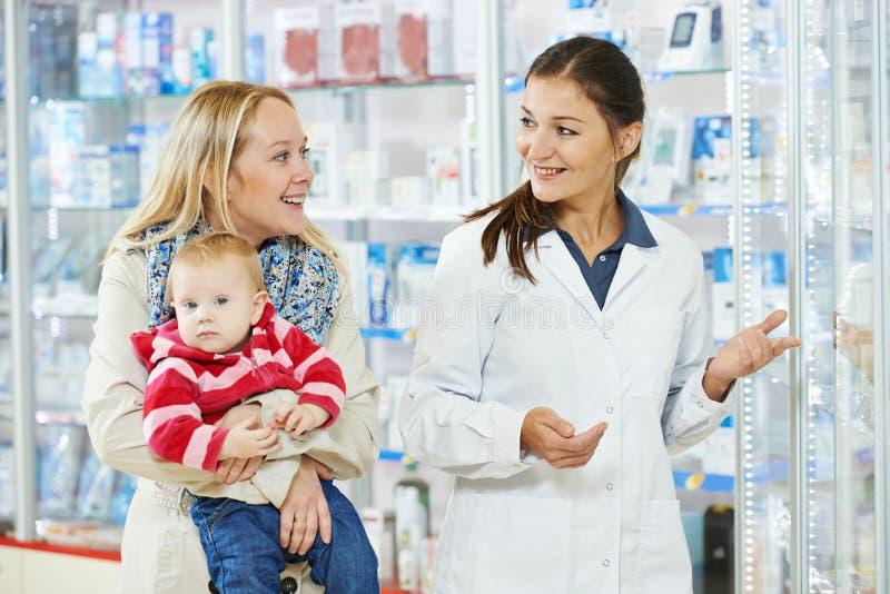 De chemicus, de moeder en het kind van de apotheek in drogisterij stock foto's