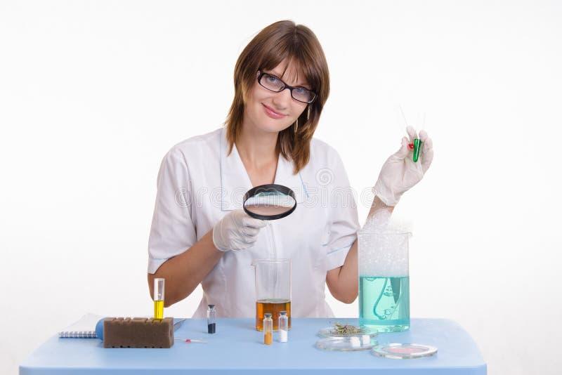 De chemicus onderzoekt de inhoud van fles royalty-vrije stock foto's