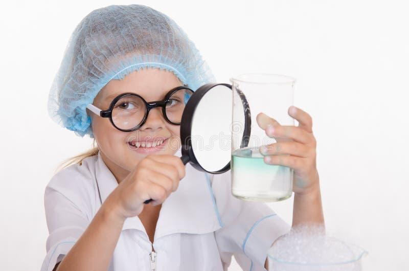 De chemicus onderzoekt een fles onder vergrootglas royalty-vrije stock afbeelding
