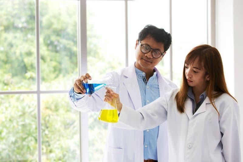 De Chemicus wetenschappelijke testende quarity van de Scienetest Wetenschapper twee die bij laboratorium werken Man en vrouw bij  stock foto