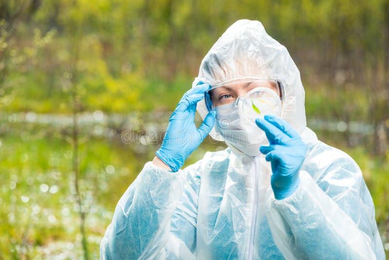 De chemicusonderzoeker in beschermende kleding onderzoekt besmette installaties royalty-vrije stock foto